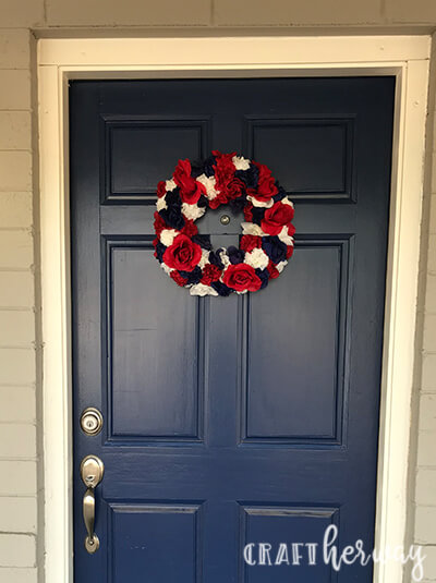 red, white, and blue flower wreath hanging on blue front door for 4th of July